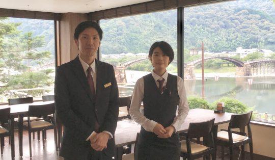 店内から一望できる錦帯橋の景色と小田統括(左)