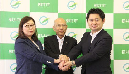 握手する小野社長(左)、坂田統括監、井原市長(右)