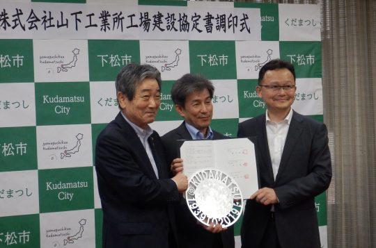 調印後の記念撮影で(左から)                    国井市長と内畠次長、山下社長